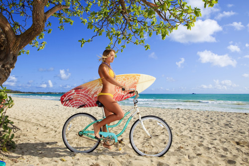 beautiful young girl on her bicycle with surfboard at kailua beach, hawaii