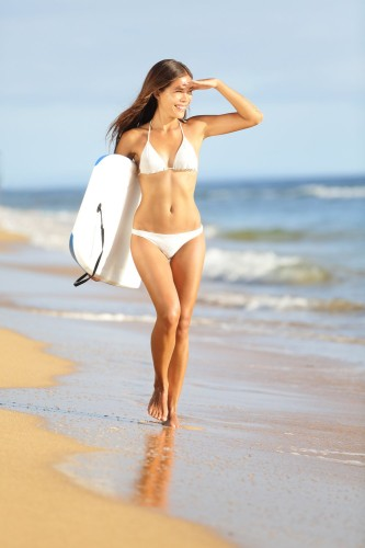 Beach fun woman going surfing with bodyboard