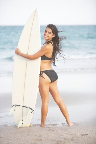 Cute Hispanic Girl holding surfboard near the ocean
